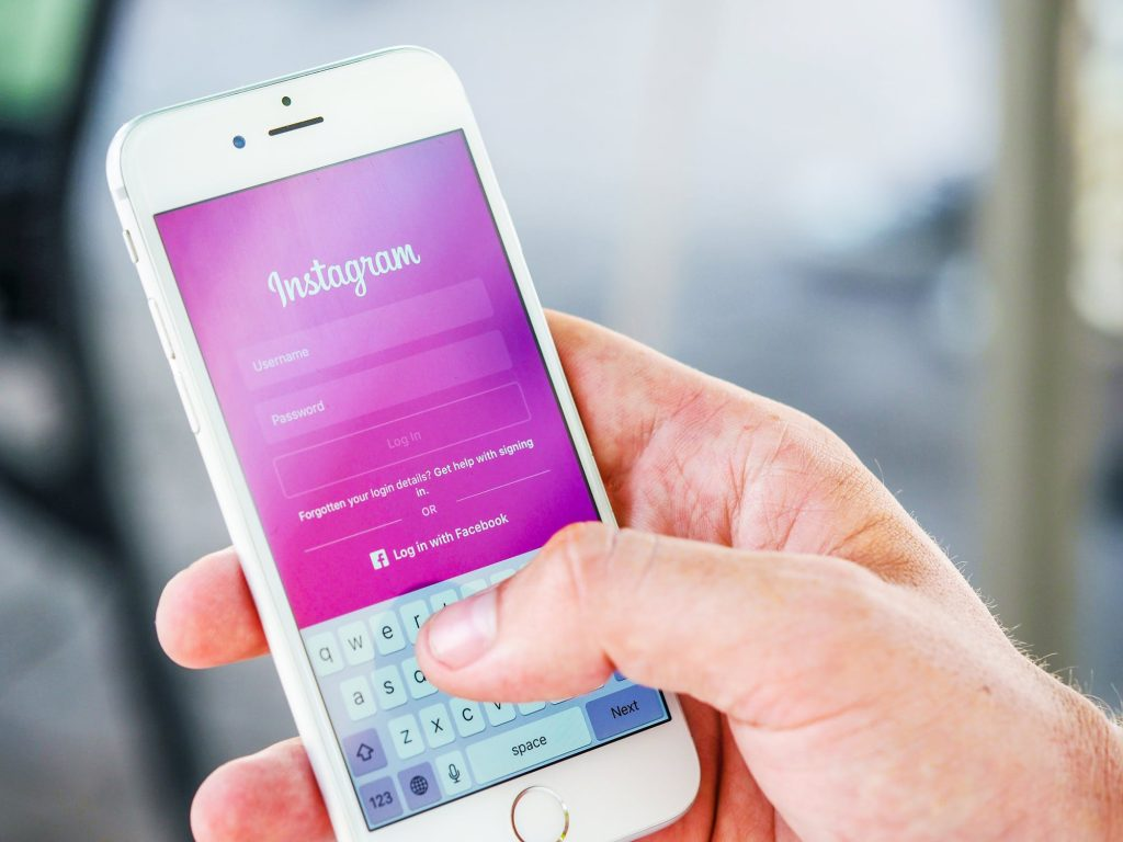 Person holding phone with Instagram App - how to promote blog posts, blog promotion