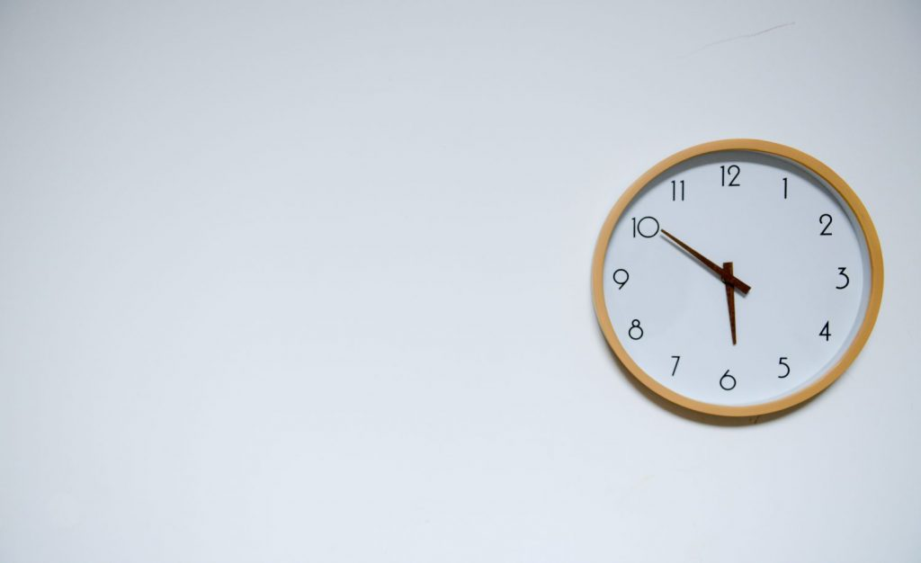 Clock on a white wall showing time