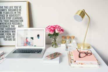 picture of a desk with a laptop, flowers, and notebooks - blog niches